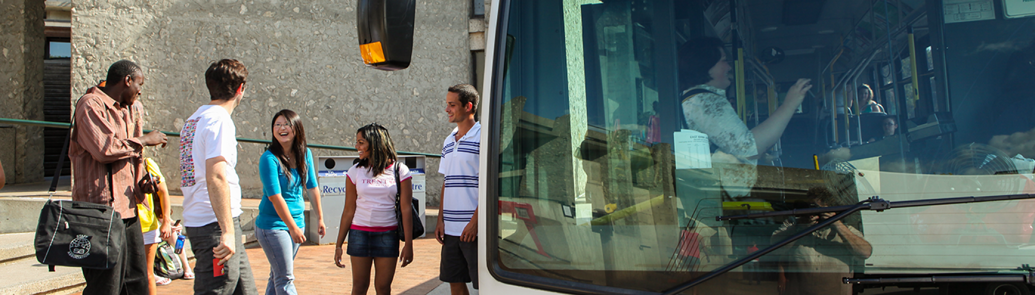 A group of 4 students about to board the bus outside of the Bata library on a sunny summer's afternoon