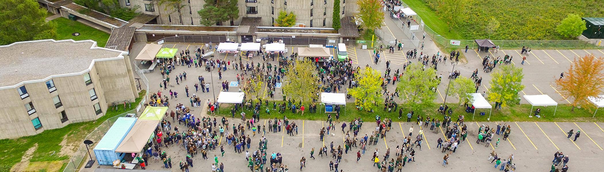 Aerial view of the beer garden in a parking lot with lots of people walking about