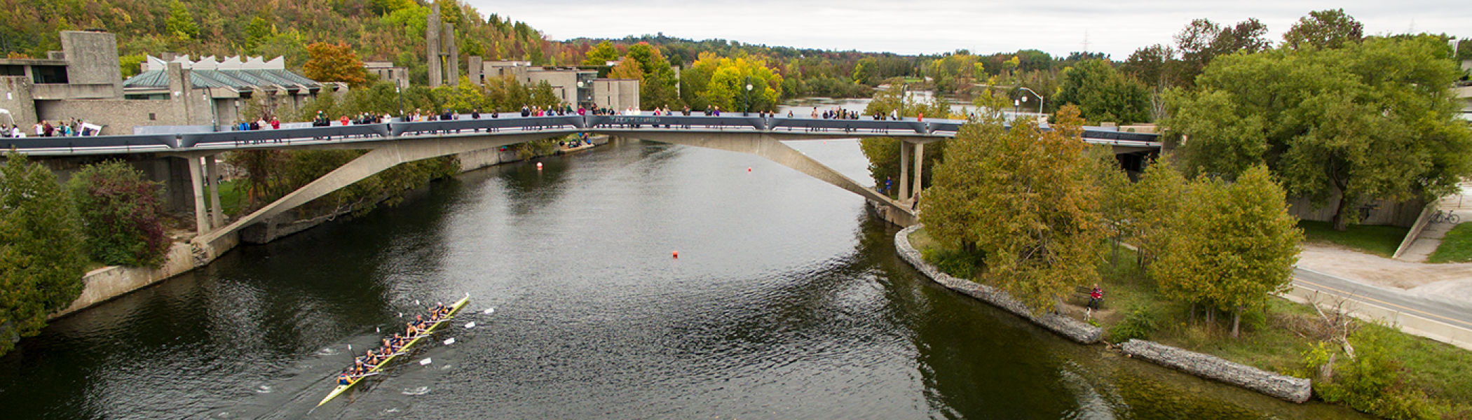 Aerial view of a scull moving up the Otonabee river past the Faryon bridge, full of people waving