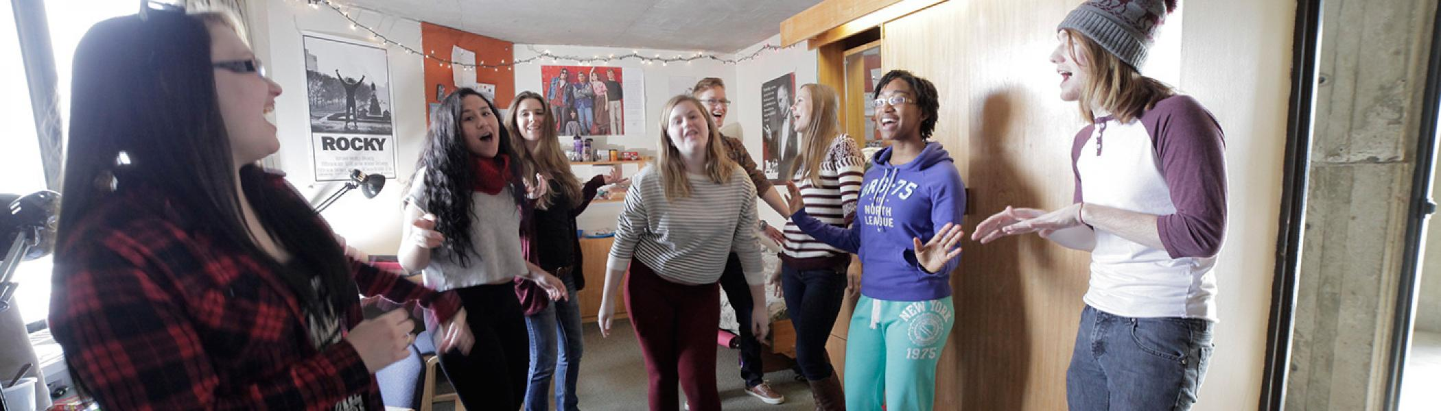 Students singing and dancing in residence room
