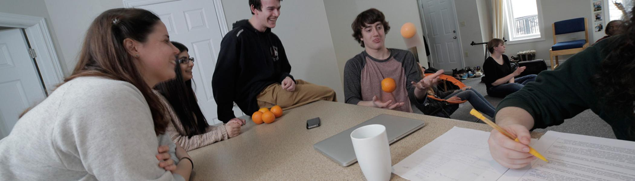 Students gathered in kitchen, one student juggling, others watching