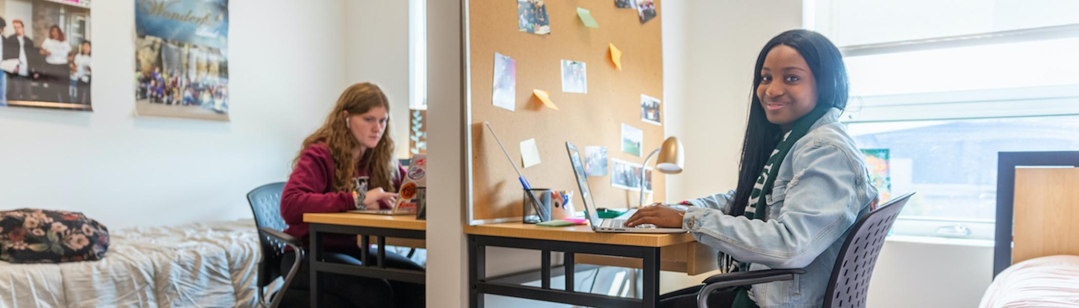 Two students studying together in their double residence room