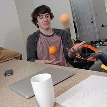 Student in residence room, juggling oranges