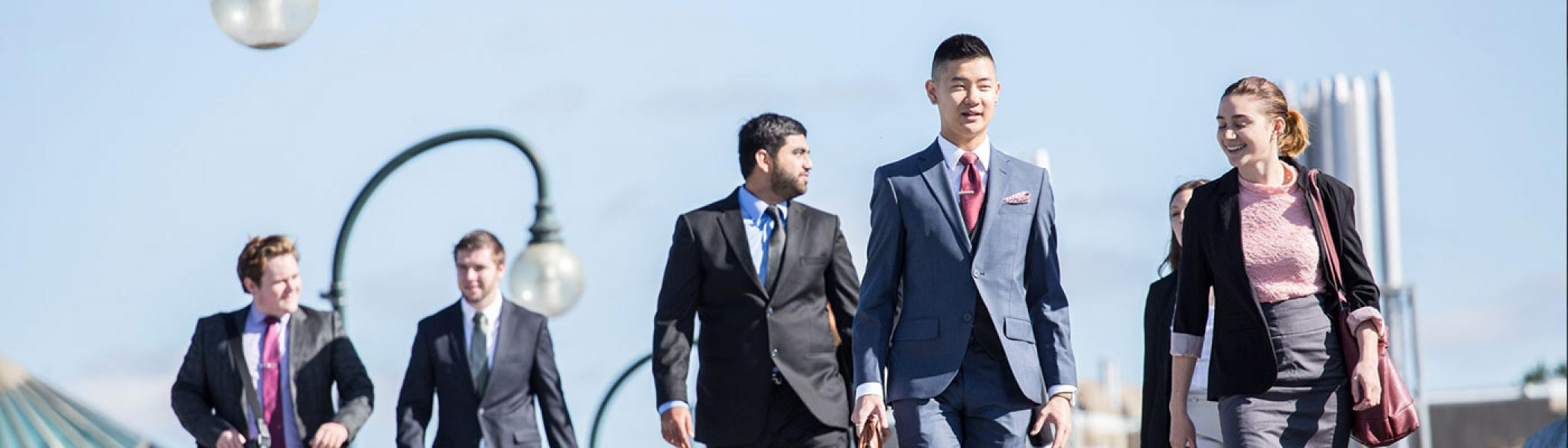 Business student walking on the bridge wearing formal clothing
