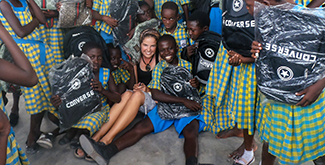 An International Development Studies students sitting on the ground in Ghana, surrounded by young children holding backpacks