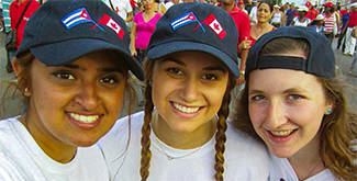 Three International Development Studies students in baseball caps, smiling at the camera in a crowded Cuban street