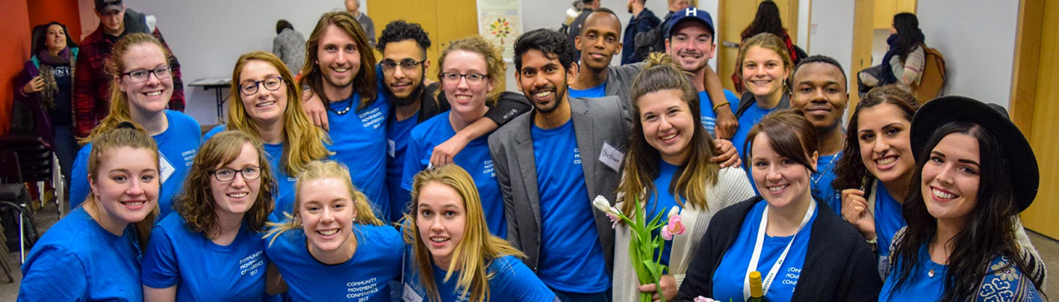 A group of students huddles together in a classroom, wearing blue t-shirts, smiling at the camera