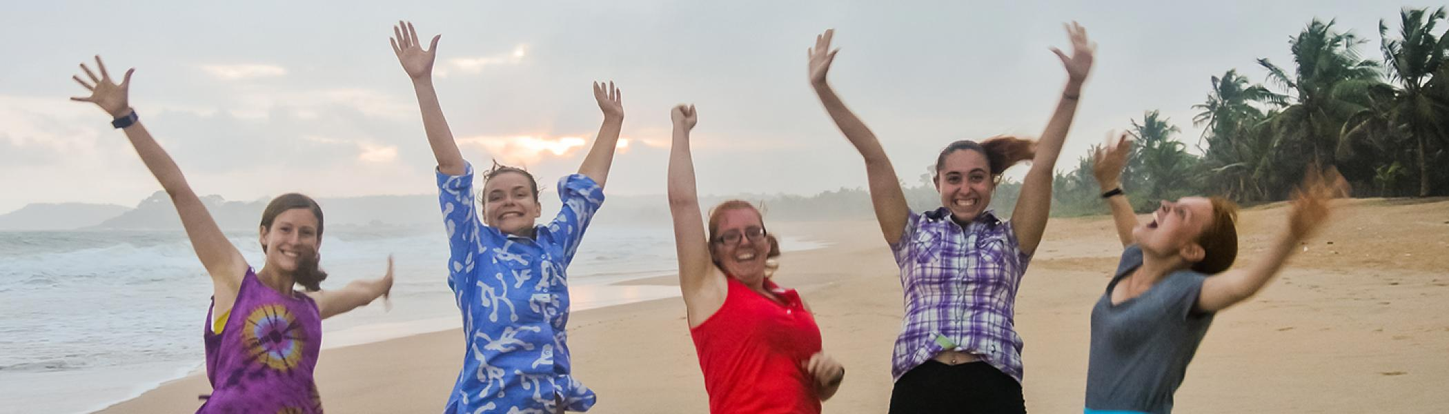 Five students on a beach, jumping in the air with their arms up