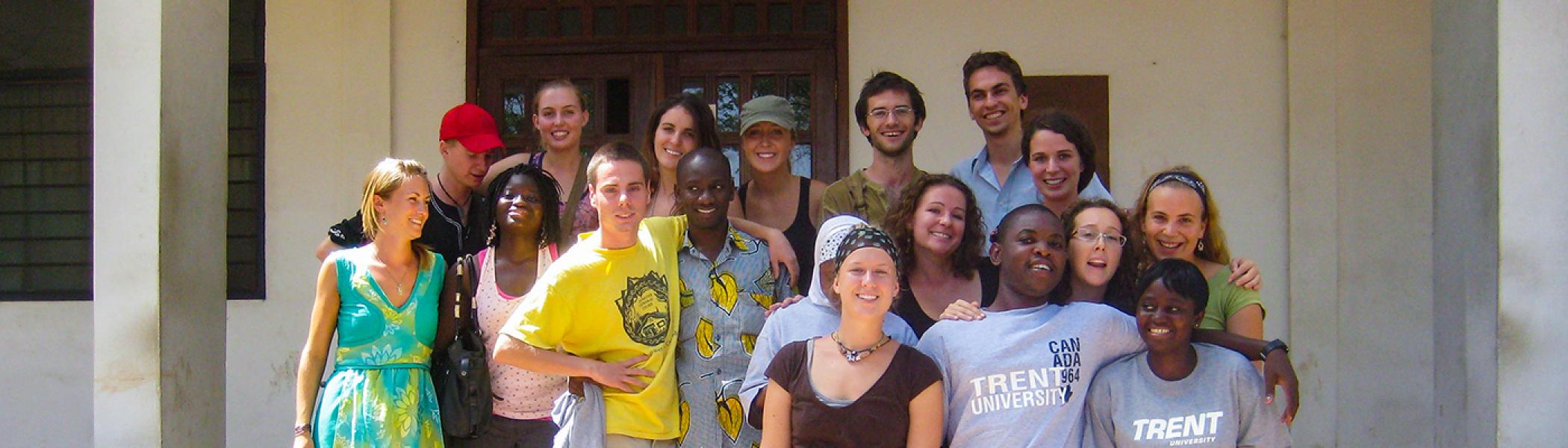 A group of International Development Studies students gathered on the front steps of a building in Ghana