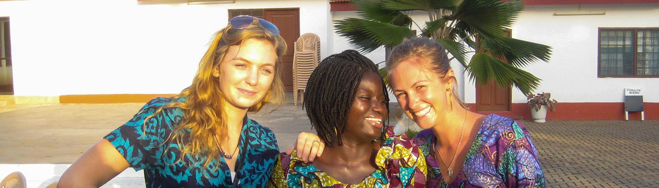 3 International Development Studies students smiling at the camera, in a Ghana yard in the sun