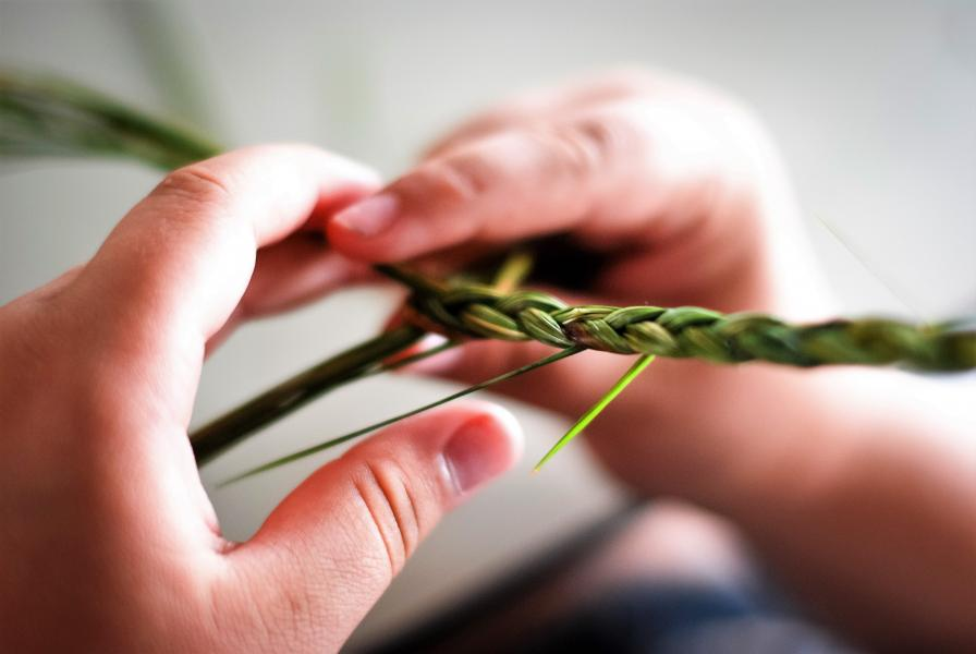 Picture of hands weaving a piece of sweet grass