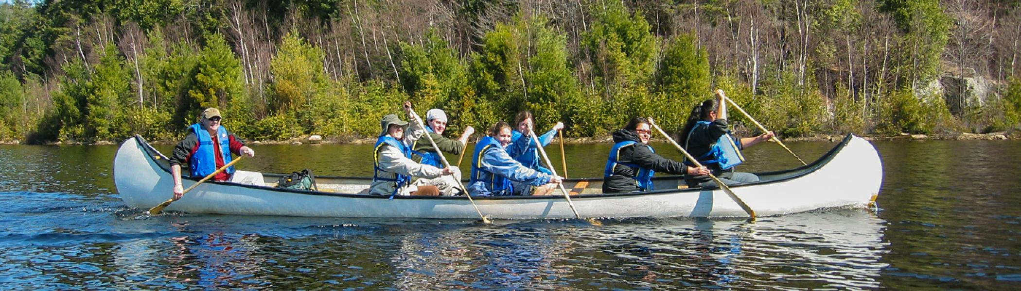 a group of people sitting in a canoe with blue life jackets on, paddling along a river in the summer sun