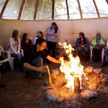 group of people sitting on chairs around a fire in the tipi (teepee) at Trent University