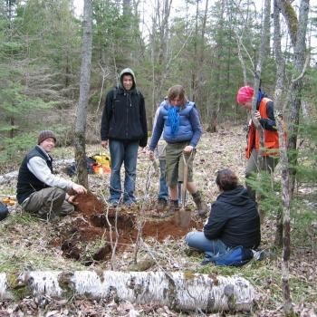 students digging hole in ground in forest in Trent Nature Area