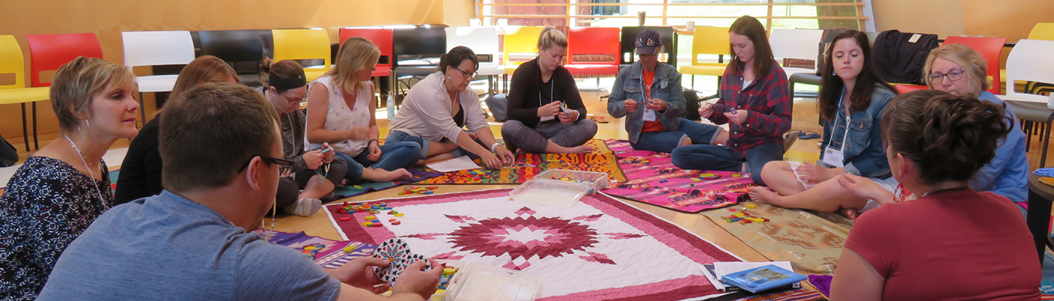 Teachers sitting in a circle working on Indigenous crafts