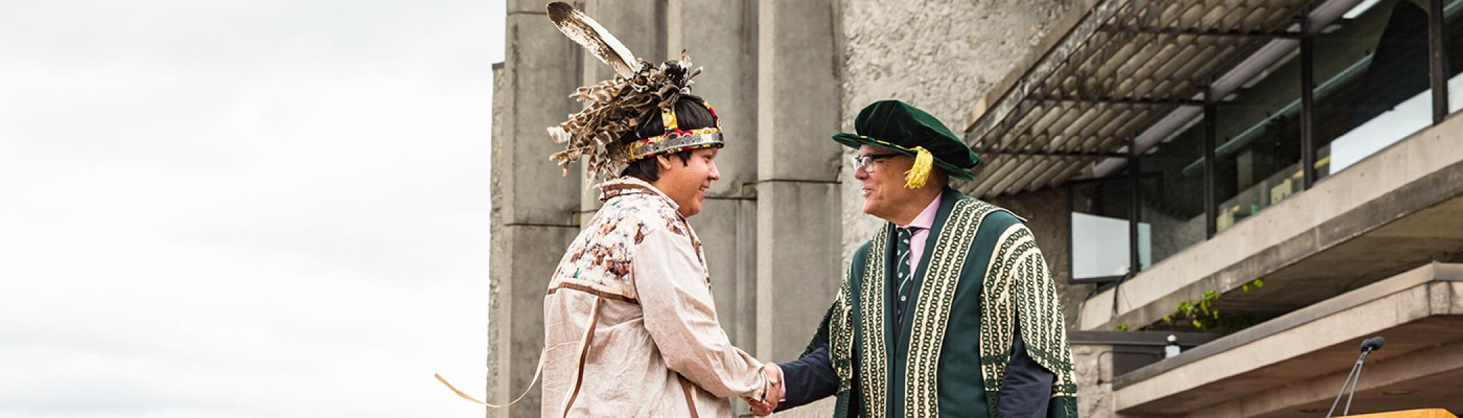 Dr. Don Tapscott shaking hands at convocation with an Indigenous Studies graduate