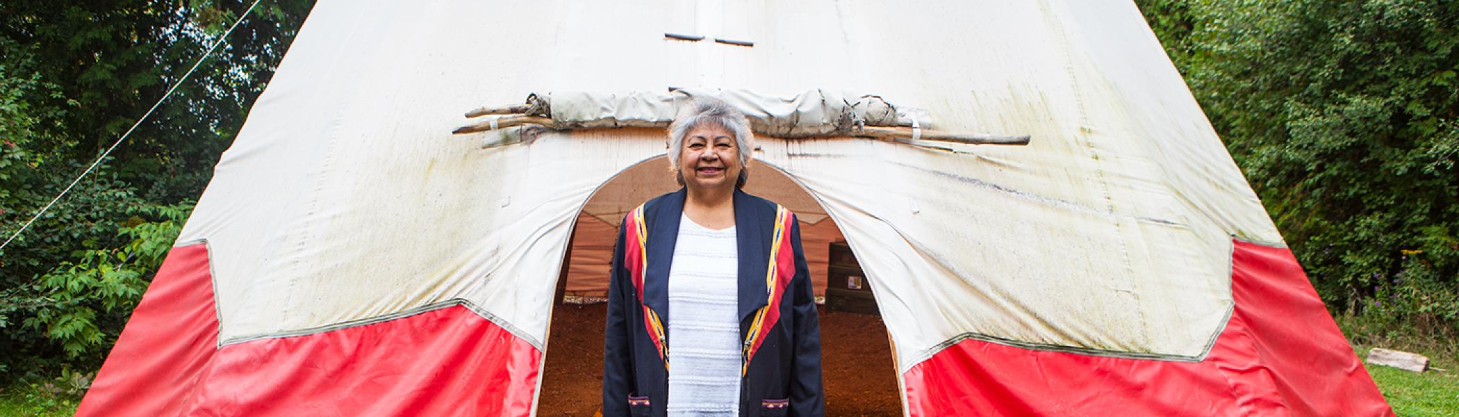 Shirley Williams standing in front of a teepee smiling at the camera