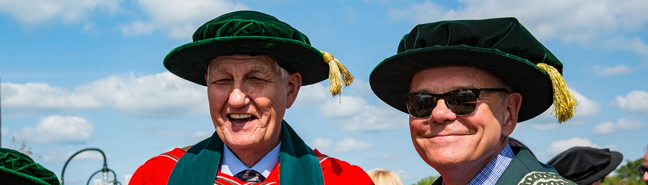 Ph.D graduate standing beside Don Tapscott, smiling at the camera following convocation