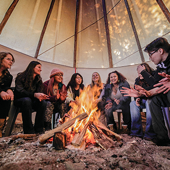 Students sitting in the tipi talking around a fire