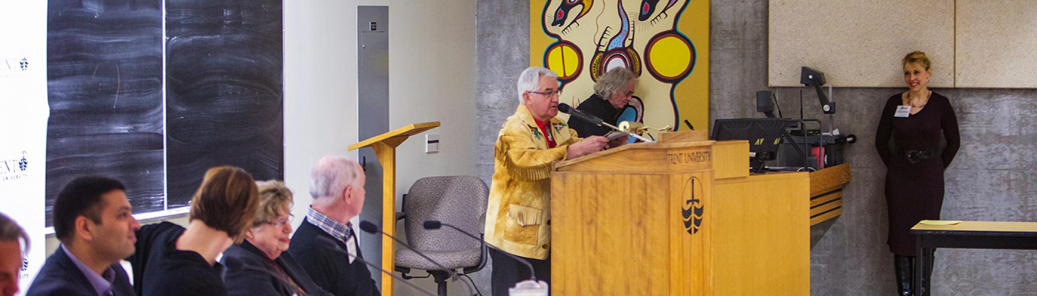 An indigenous professor standing at a podium talking to an auditorium of people