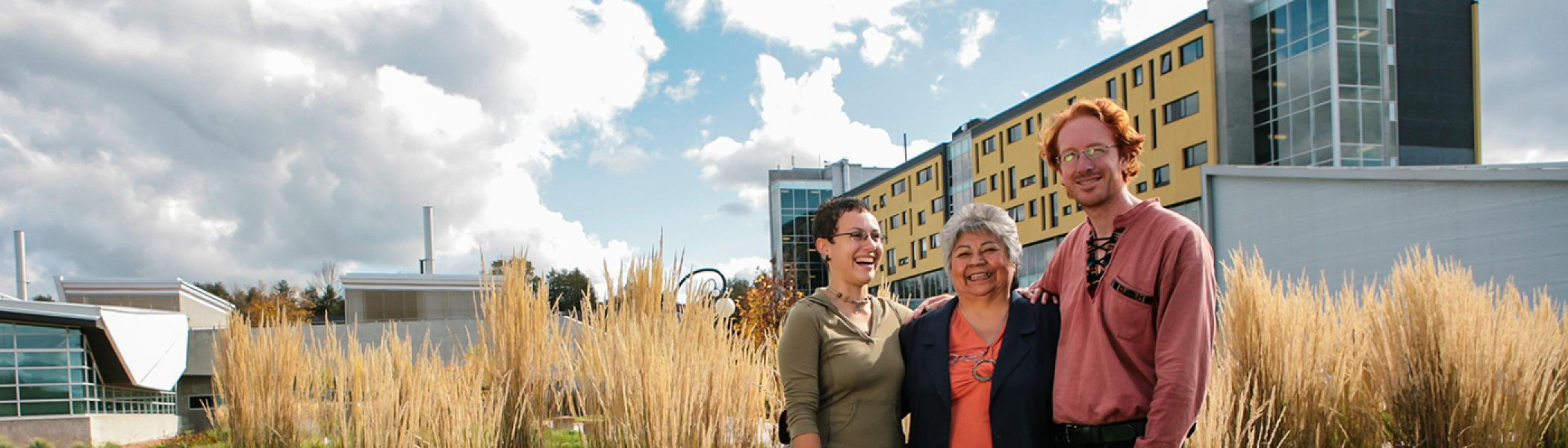 Shirley Williams standing outside in front of Gzowski College with two Ph.D. students