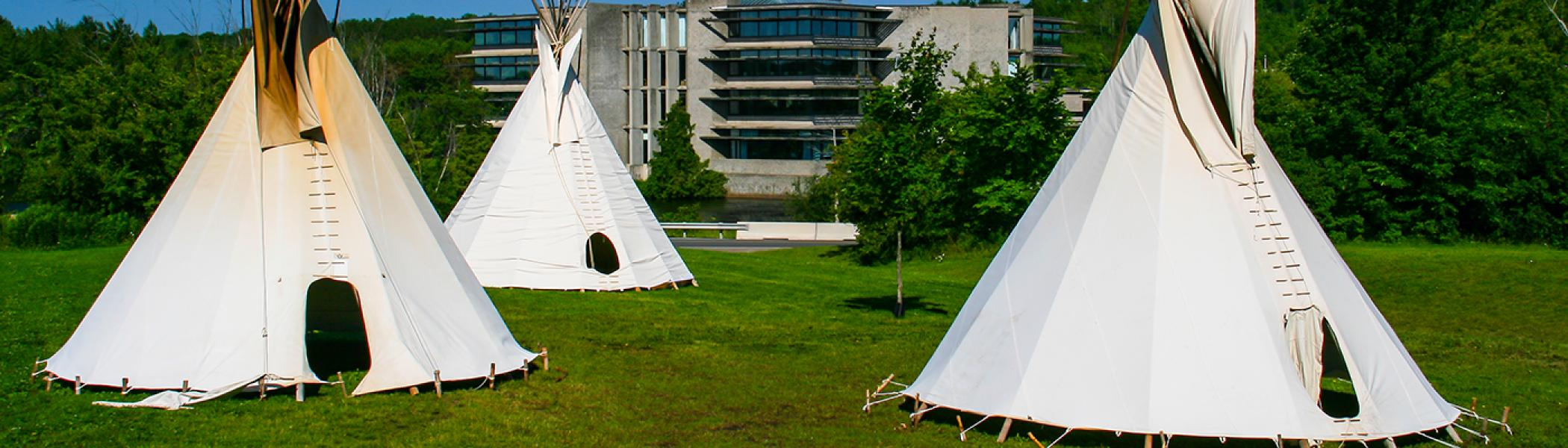 3 Tipis set on a grassy hill overlooking the Bata Library in the summer daylight