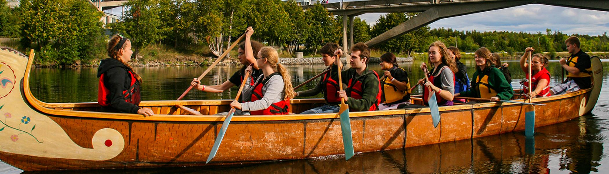 A group of students in an indigenous canoe paddling along the Otonabee river