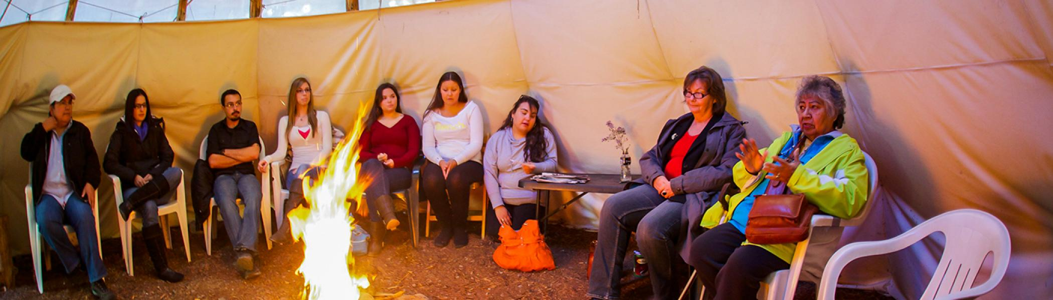 Shirley Williams sitting in a tipi in front of a fire teaching as students listen in sitting around the circle