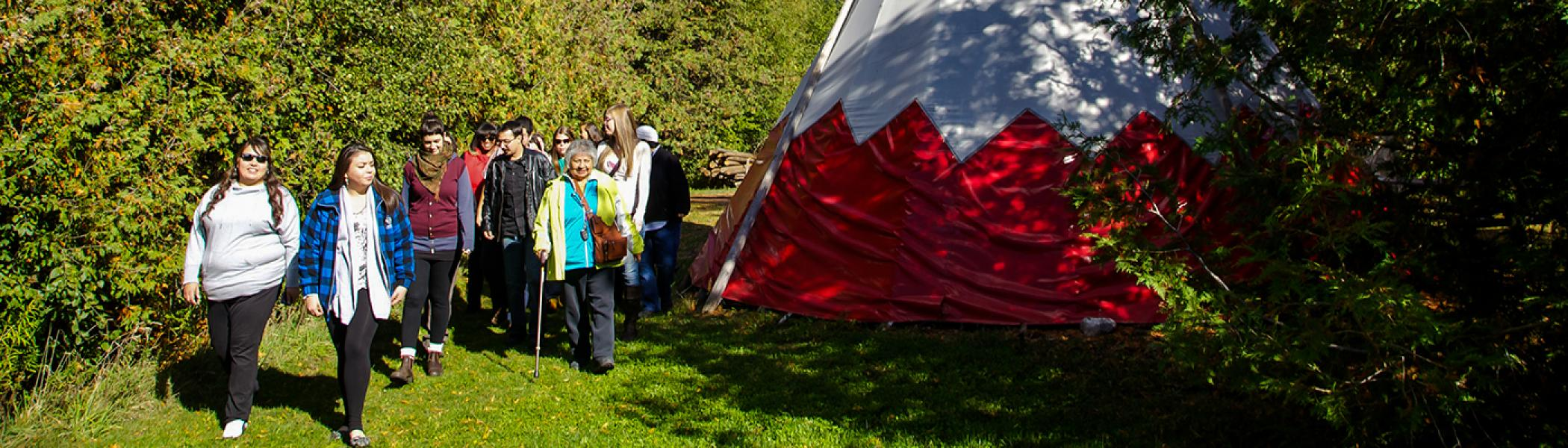 Shirley Williams walking in a forested area with a group of students in front of a tipi