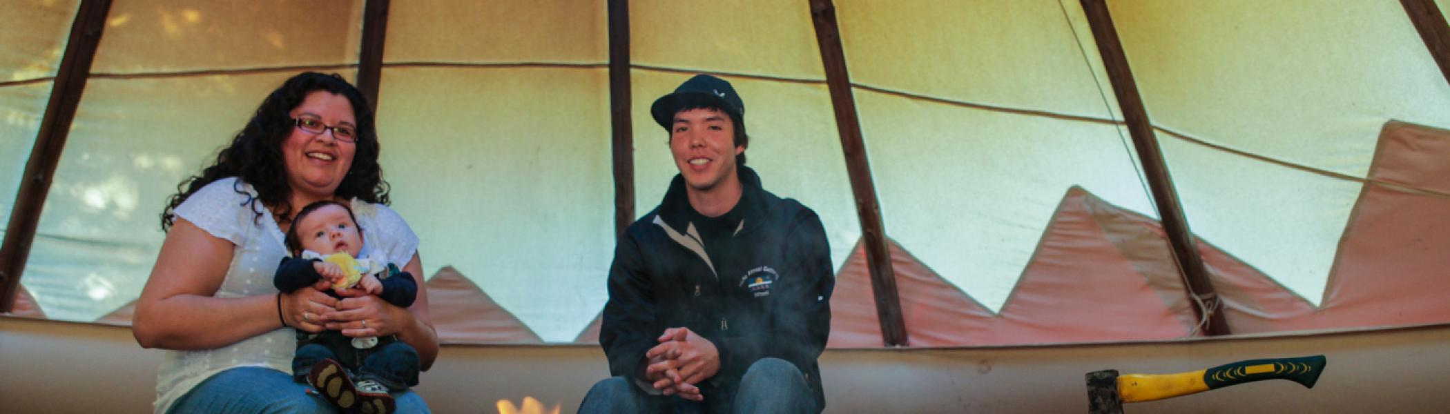2 Students sitting in a tipi in front of a fire, smiling at the camera