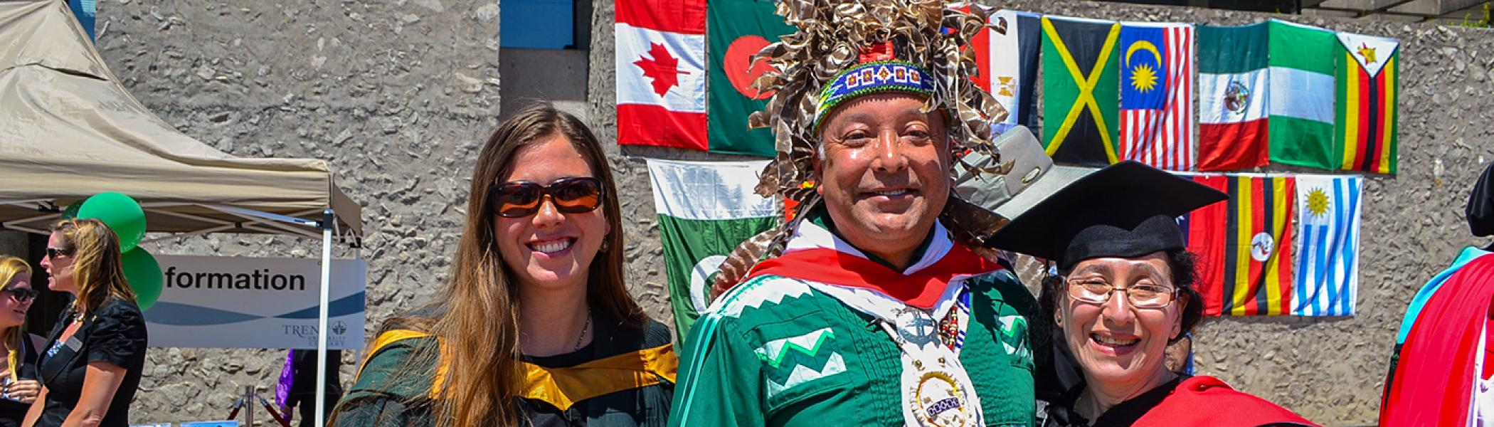 Dan Longboat, Lynne Davis and an IESS graduate smiling at the camera in front of a wall of flags during convocation