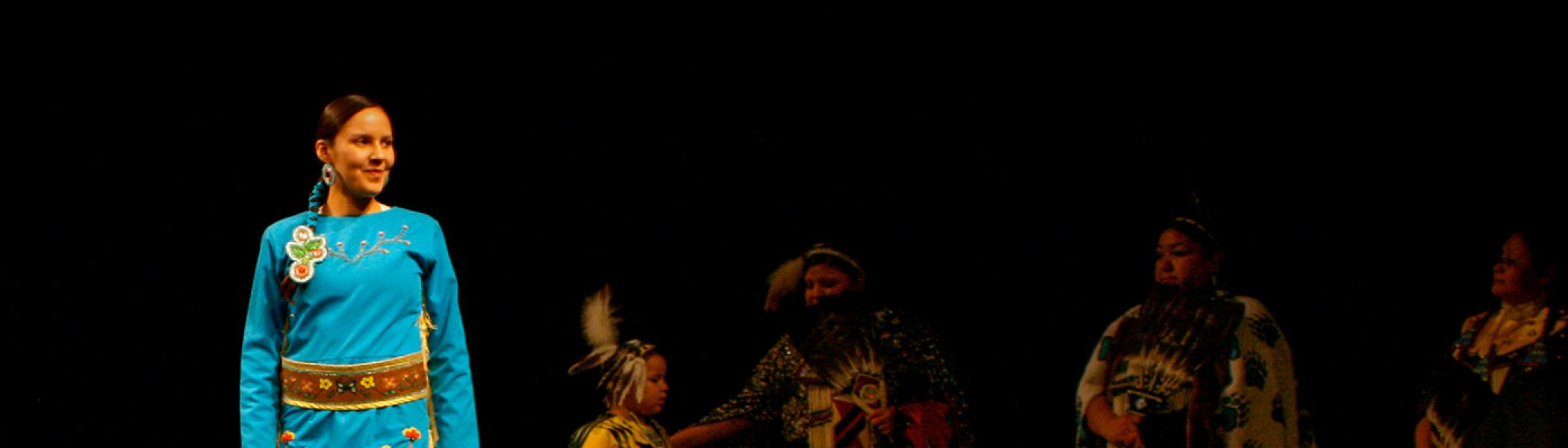 A student in the Performance Space in regalia performing a dance
