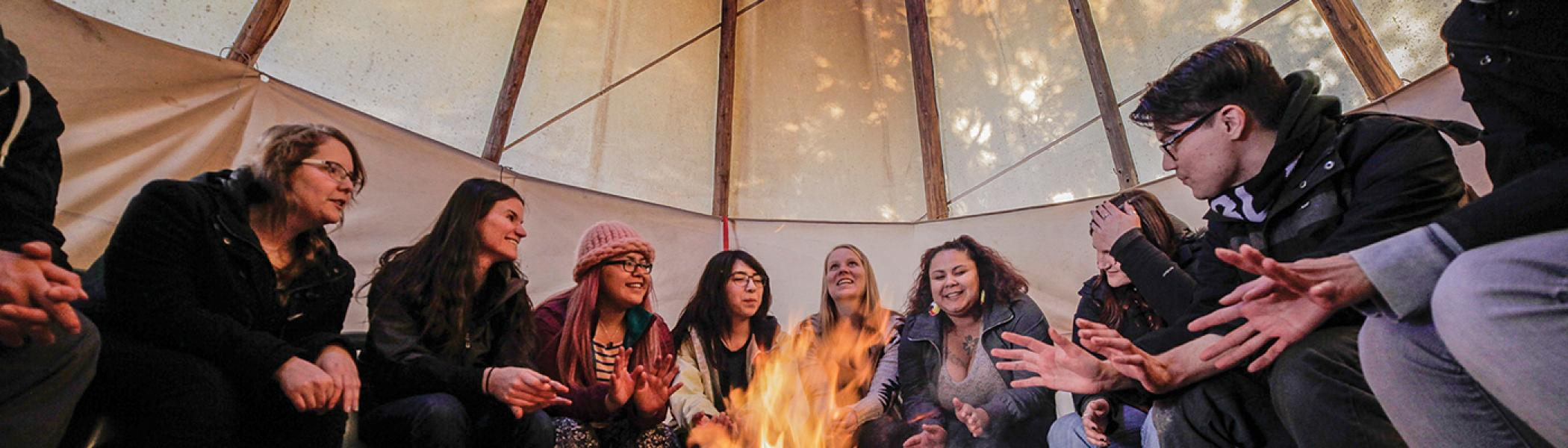 A group of students sitting around a fire in a tipi listening to a professor speak