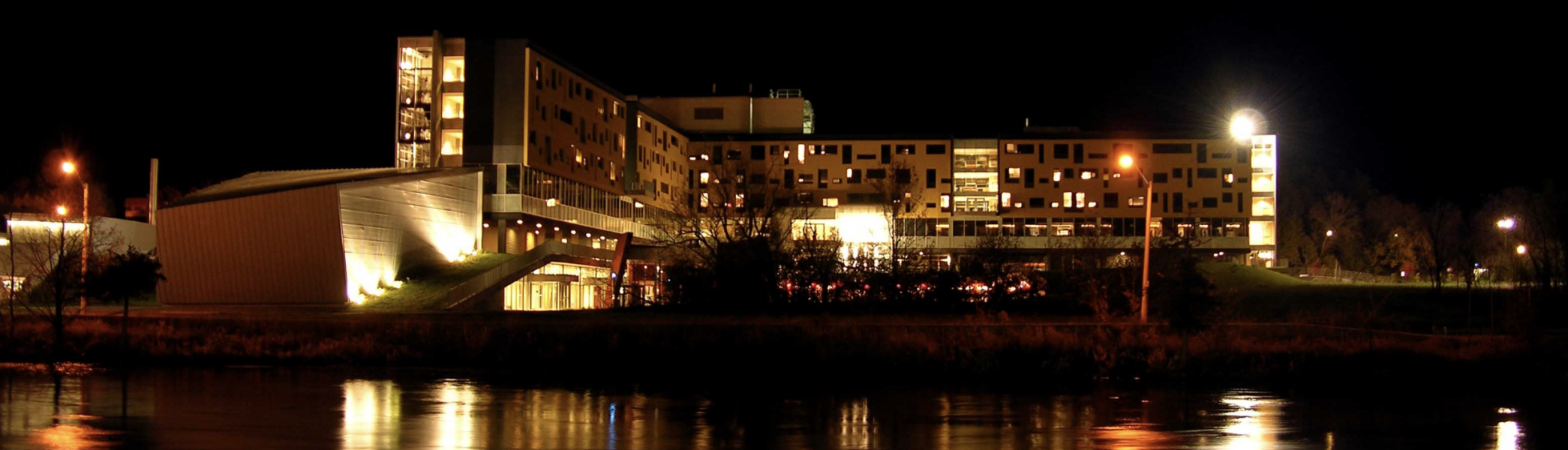 Gzowski College at night with lights reflecting off the Otonabee River