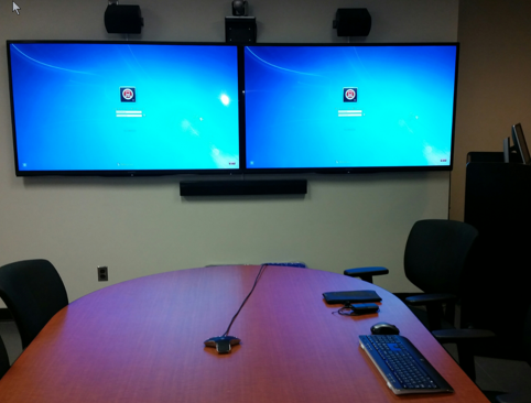 Front view of room with  two 70 inch flat panel displays, speakers, video camera,  tabletop microphone, wireless microphone, wireless keyboard and mouse, table, chairs, lectern