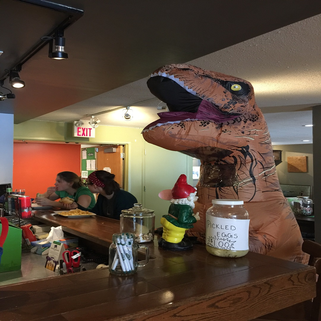 Trentasaurus Risk at restaurant counter with with bottle of pickled eggs and gnome in front. Two girls sit further down counter eating.