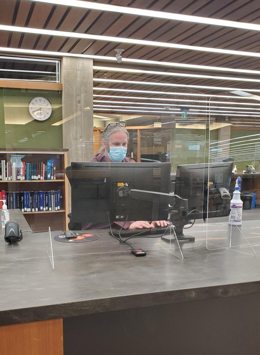 Staff working behind protective barrier at Bata Library