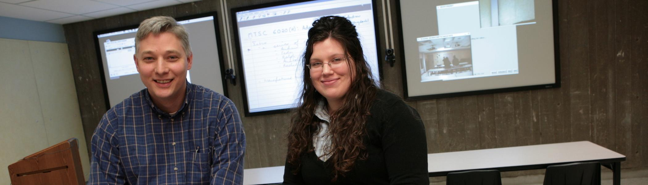 A faculty member and a graduate student sitting on a desk and smiling