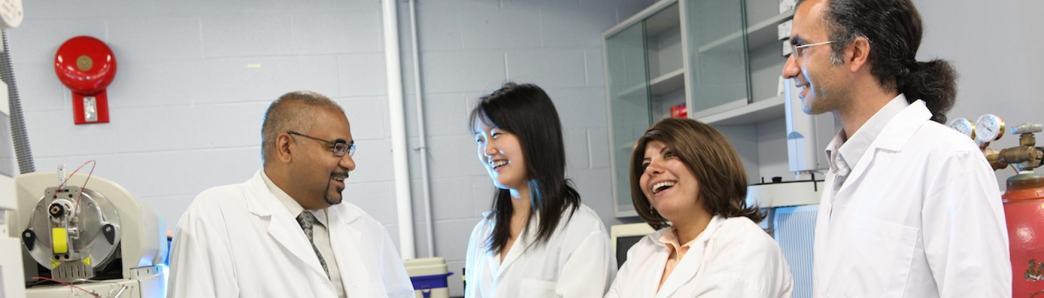 4 faculty members wearing white labs coats, looking at each other and smiling