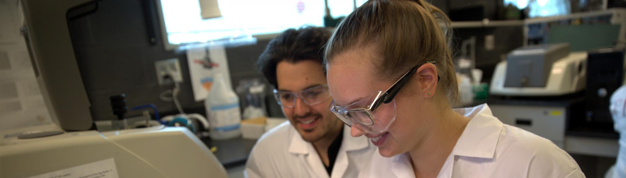 2 students wearing lab coats and glasses looking down at something and smiling