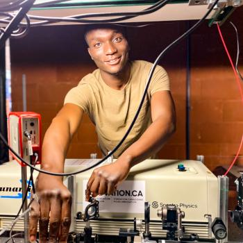 grad student working in laser lab, smiling at  camera