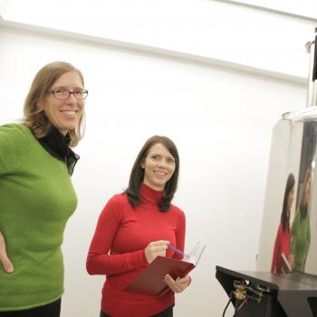 student and supervisor smiling at the camera while observing a lab experiment