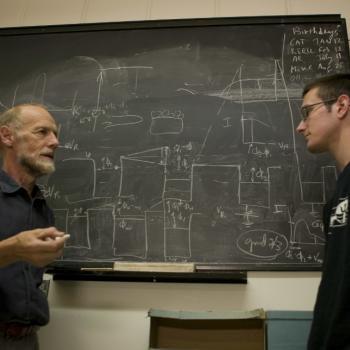 student and professor conversing in front of chalkboard with text and equations on it
