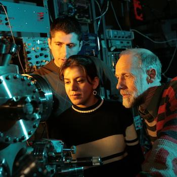 Two students and a professor looking at a large metal machine looking serious