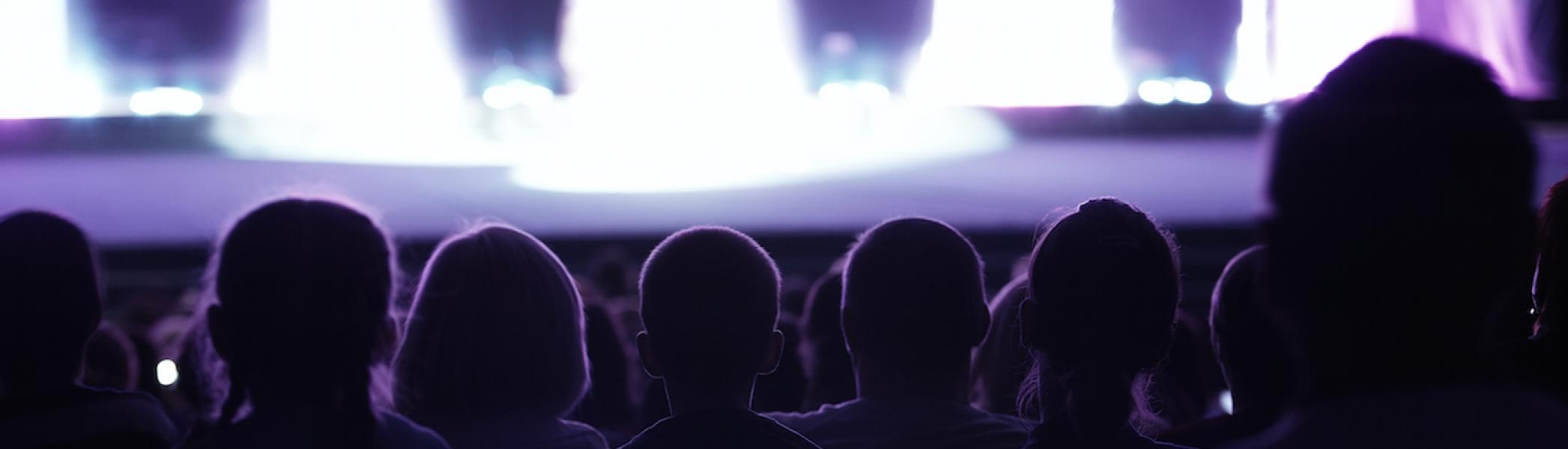 The view of a stage with bright lights from behind a row of people in a theatre.