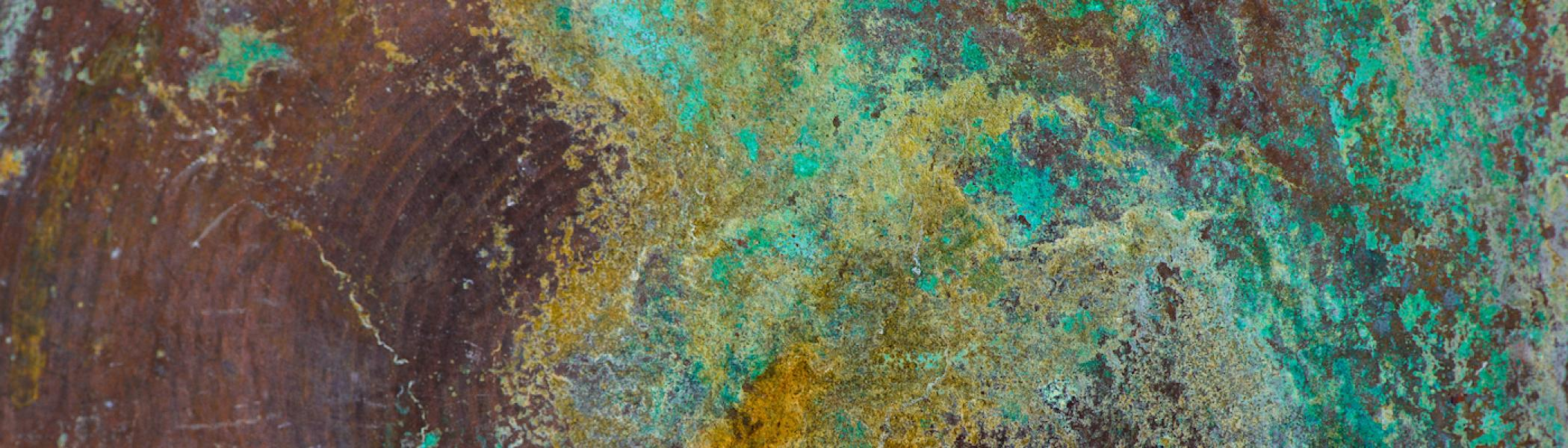 A tin background with blue, green, and gold paint swirled on it.