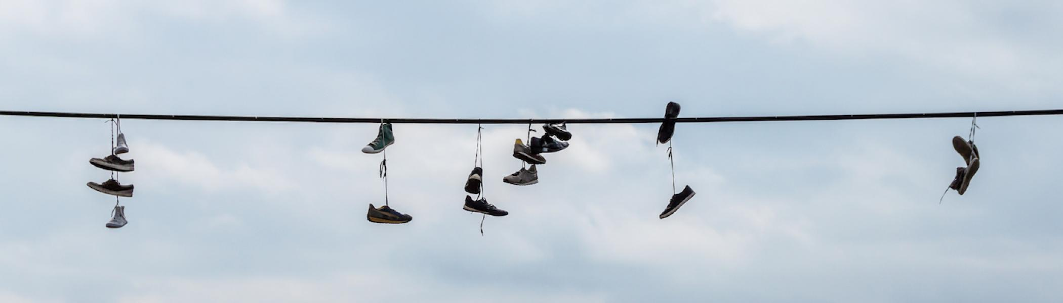 A telephone wire with 8 pairs of sneakers hung over it.