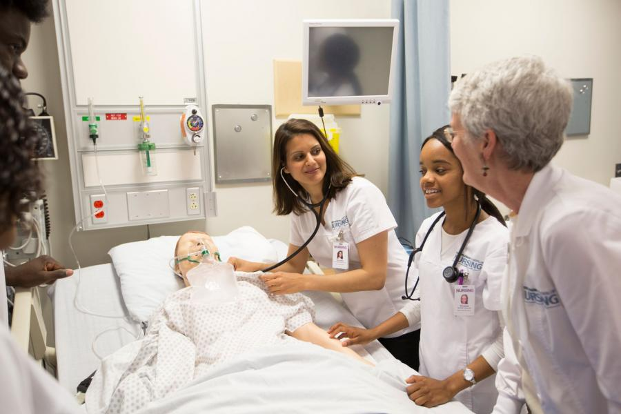 Dean of nursing and students in lab.