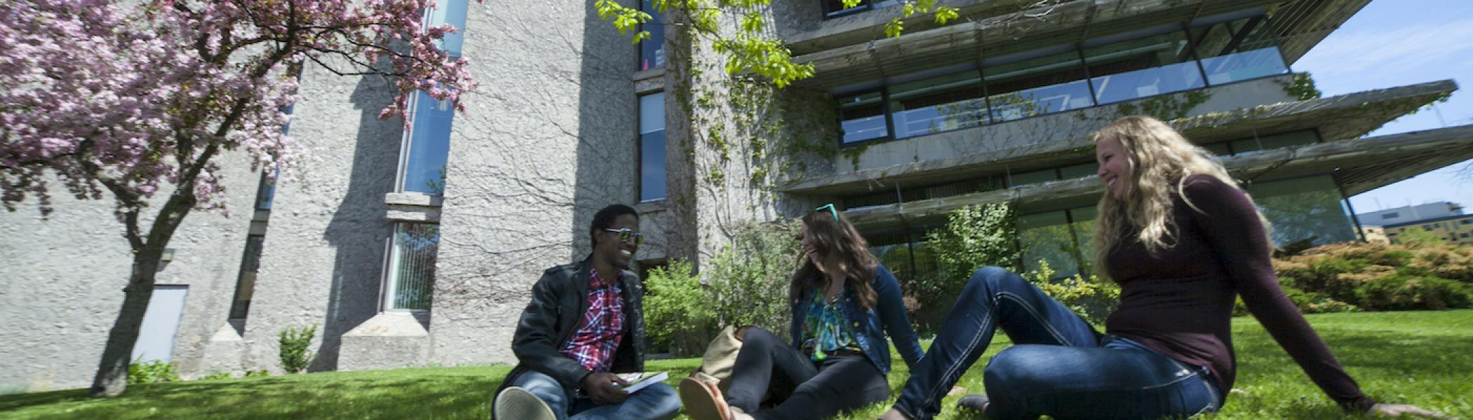 couple of student sitting and chatting in front of Bata Library on a sunny day