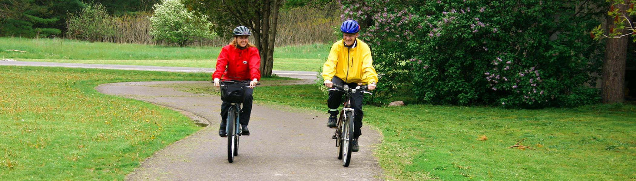 Two people biking on a path towards the camera